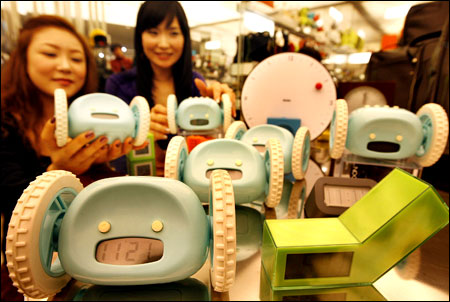 "Customers take a look at ""Clocky"" alarm clocks at an outlet of Shinsegae Department Store in Seoul"